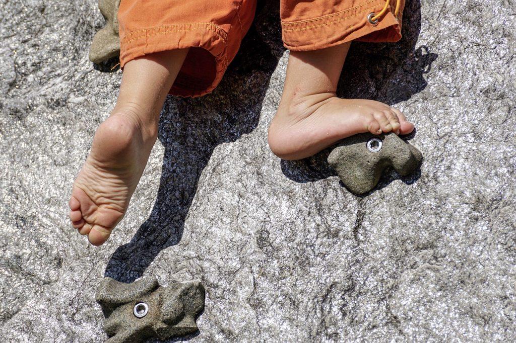 a barefoot child climbing rocks