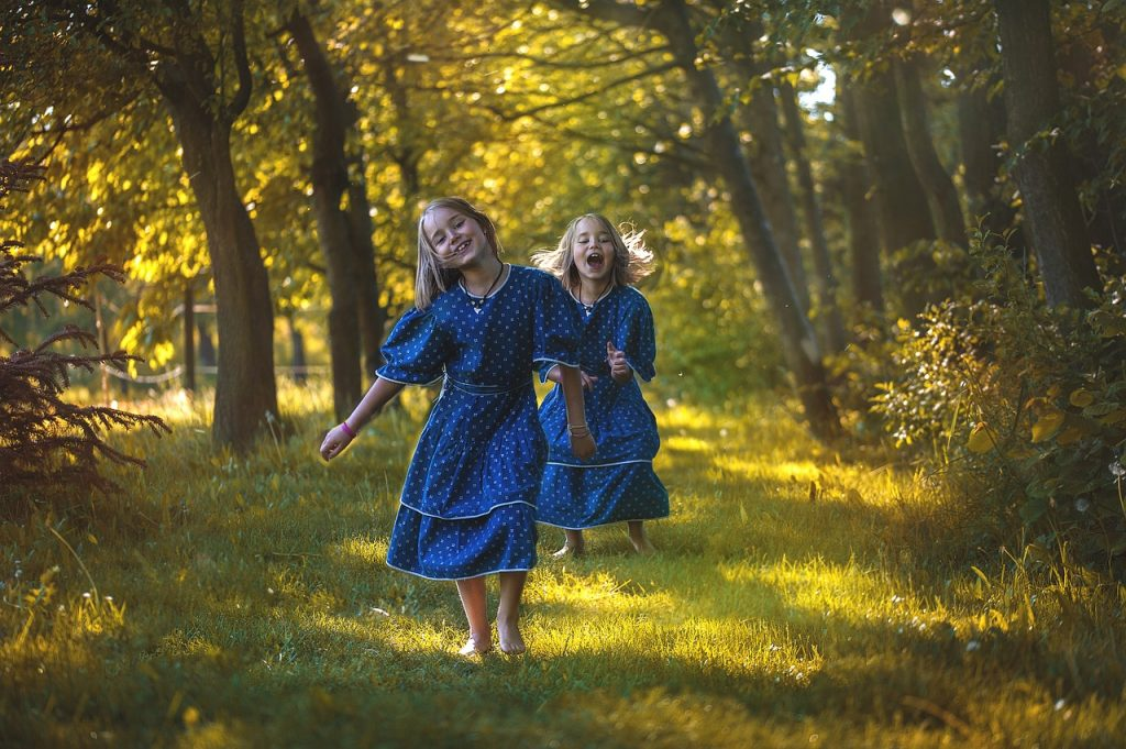 young girls run barefoot in the forest with blue dress