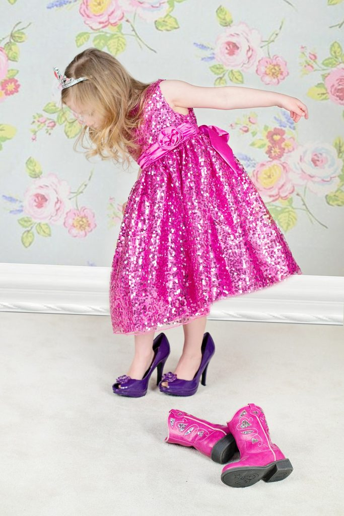 a young girls is trying up high heels in a pink dress